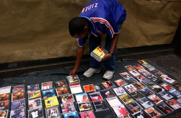 393184 09: A dealer of counterfeit pop and rap music CDs sells his merchandise August 13, 2001 on a street in New York City. Constantly keeping one eye out for the police, these wandering dealers of knock-off CDs, purses, sunglasses, watches and videos can be found by the dozens in any of the tourist districts of New York City. (Photo by Spencer Platt/Getty Images)